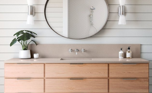 rose quartz countertop colors with natural wood cabinets, integrated sink, oval mirror, white sconces, plant in white pot, white shiplap walls.