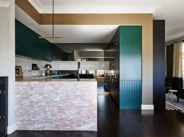 Pink quartz countertop colors, teal cabinets, and dark wood floors