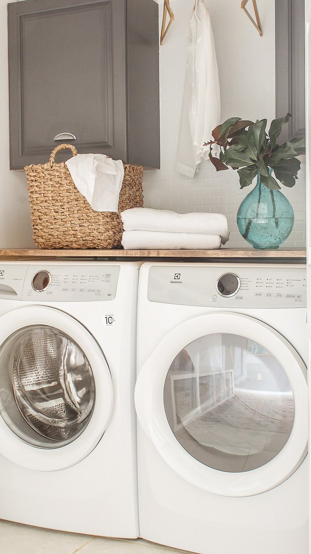 washer and dryer with basket and plant on top for basement laundry room ideas.