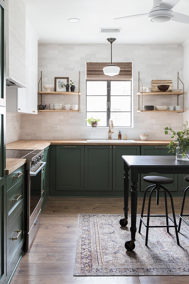 Traditional kitchen design with green cabinets and white tile backsplash