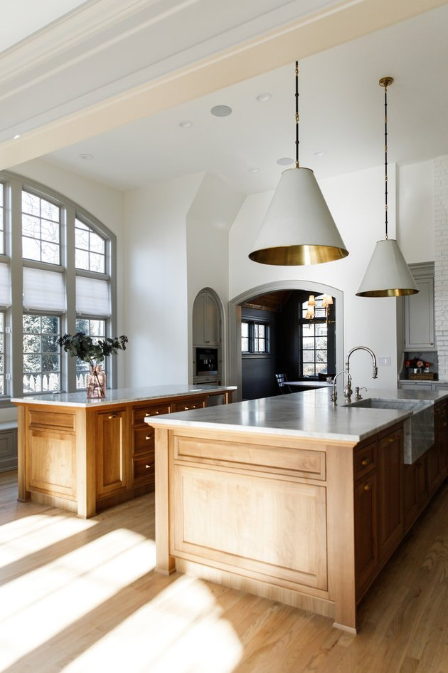 Traditional kitchen design with large white and brass pendant lights and two islands