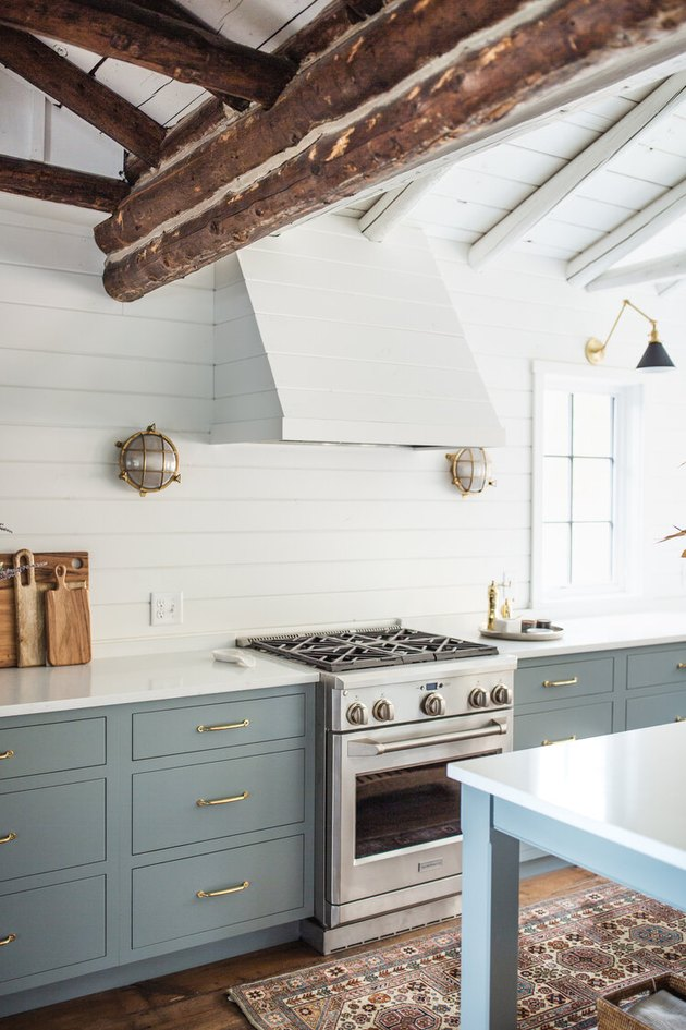 Traditional kitchen design with reclaimed timber ceiling beams and blue cabinets