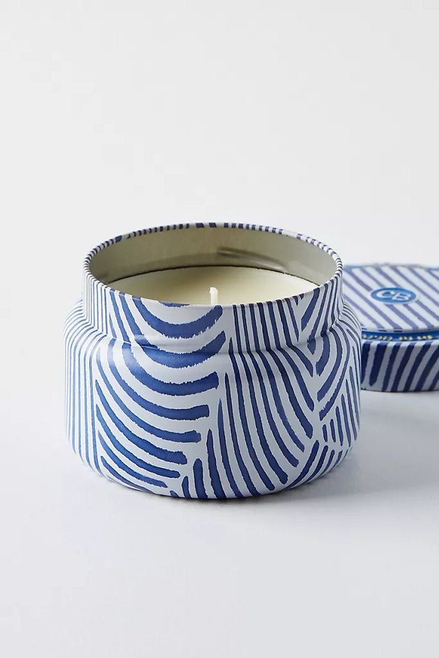 light candle in blue patterned tin
