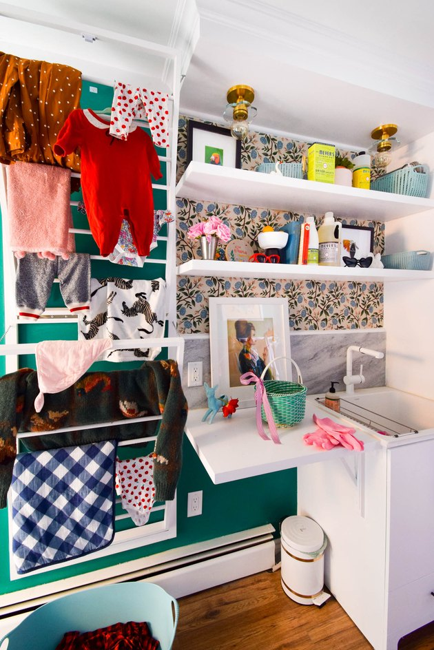 basement laundry room ideas with cool vintage art and clothes on a drying rack.