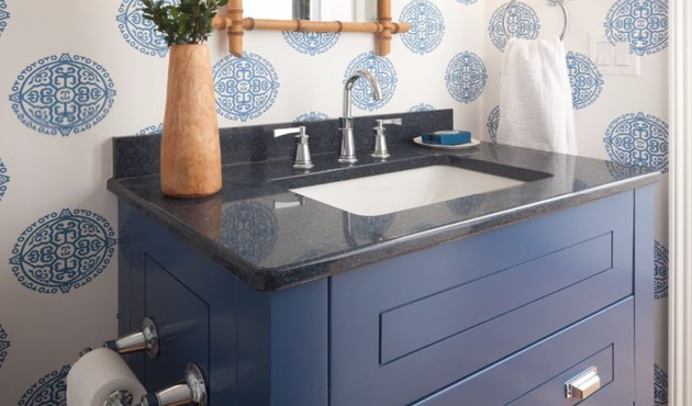 Navy quartz countertop colors with blue cabinet, blue patterned wallpaper, vase, bamboo mirror.