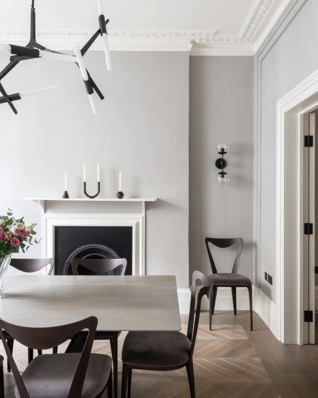 soft gray neutral colors in dining room with fireplace and white mantel