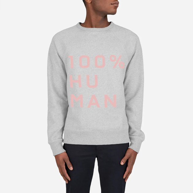 person wearing grey shirt with pink text reading 100% human
