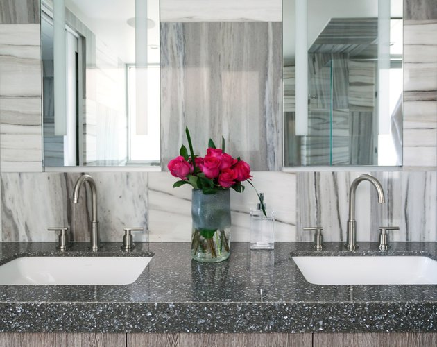 Black and white quartz countertop colors, double white sinks, marble backsplash, large mirror.