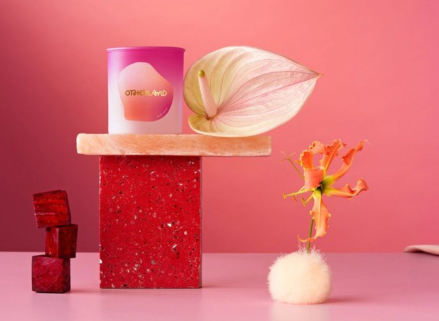 pink candle on a pedestal with flowers nearby