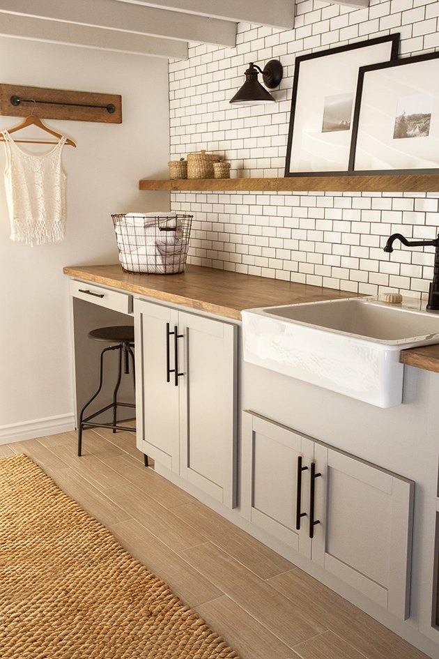 country-chic basement laundry room ideas with white subway tile and gray cabinets