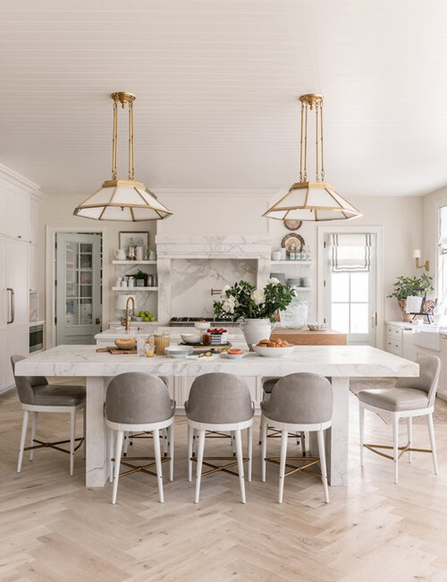Traditional kitchen design with white and brass pendant lights and dining table