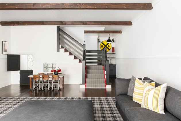 rustic basement ideas with wooden beams, white paint, and gray furniture