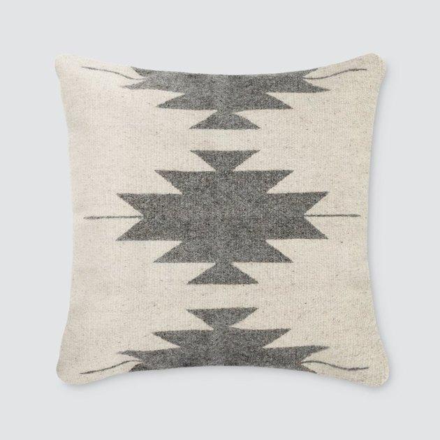 Off-white throw pillow with gray Aztec print