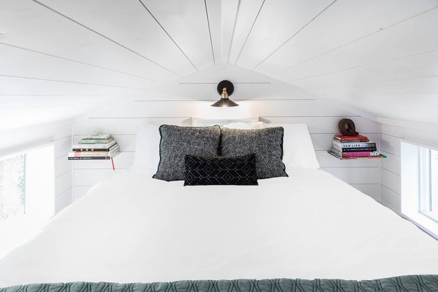 modern tiny house with white bedroom in attic like spot with two floating shelves