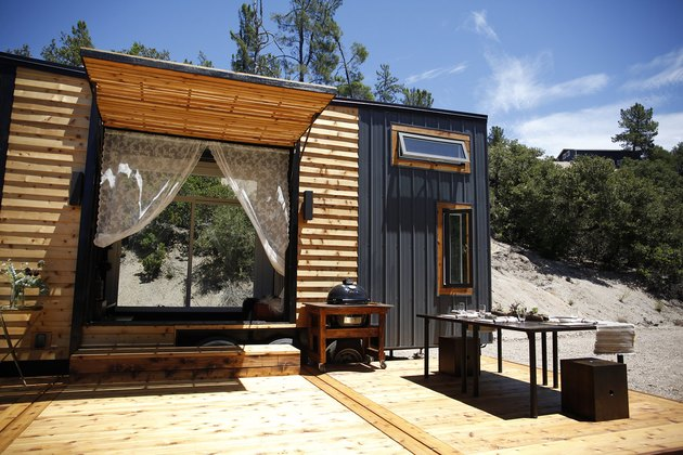 black and wooden modern tiny house with outdoor dining area