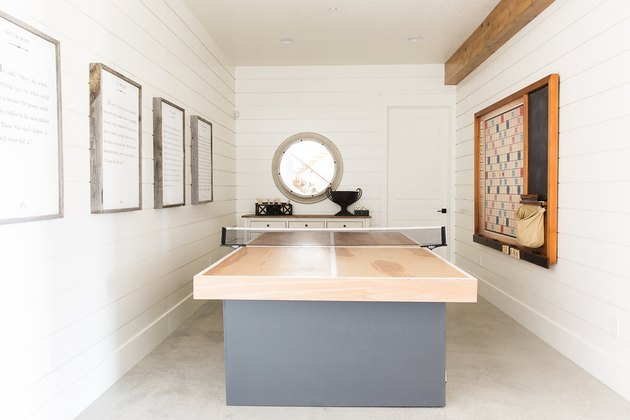 attic game room with light wood and gray ping pong table, concrete floors, white walls, round window.