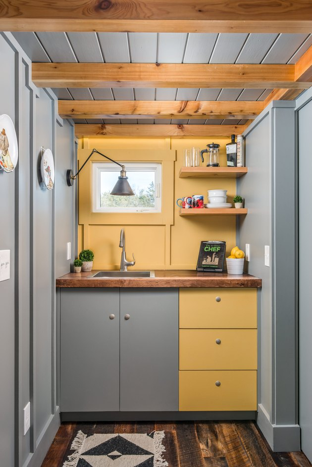 modern tiny house with yellow and gray kitchenette