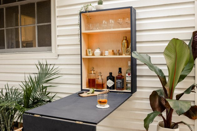 DIY outdoor Murphy ball folded down on wall and stocked with liquor and barware
