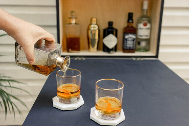 Pouring whisky into two cocktail glasses set on tabletop of Murphy bar
