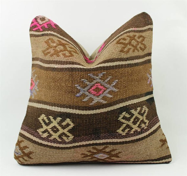 Brown and beige desert-inspired throw pillow with hot pink accent