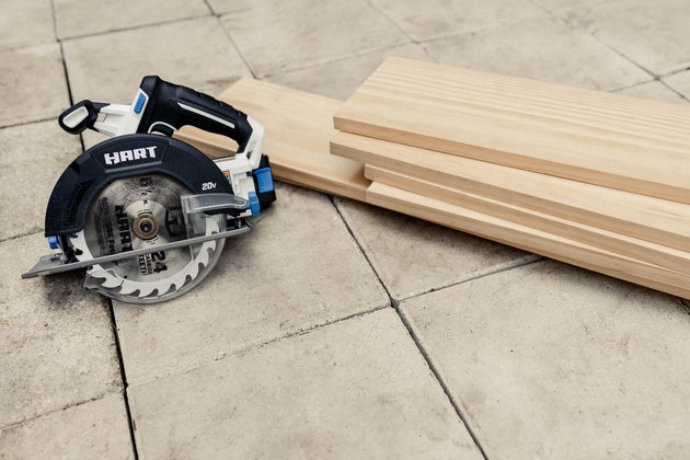 Wood boards stacked on patio floor next to HART circular saw