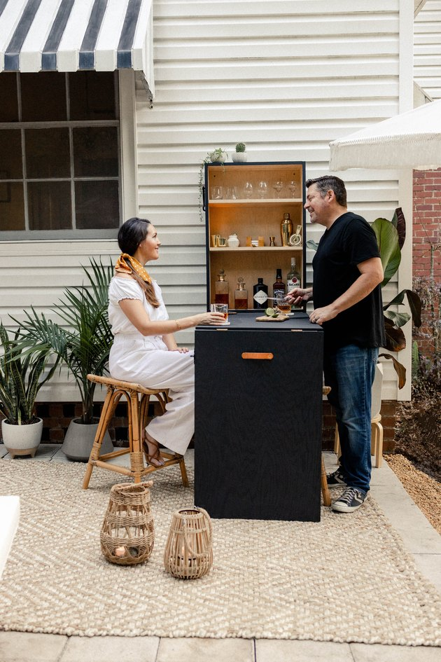Woman seated and man standing at outdoor Murphy bar on patio enjoying cocktails