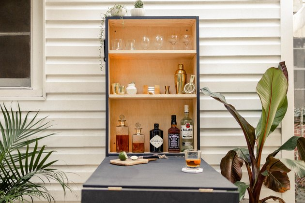 DIY outdoor Murphy bar attached to patio wall and stocked with liquor and bar supplies