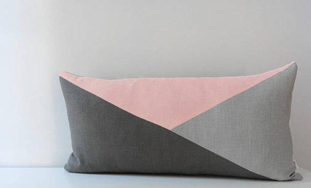 geometric lumbar pillow featuring three different-shaped triangles in light pink, light gray, and dark gray respectively