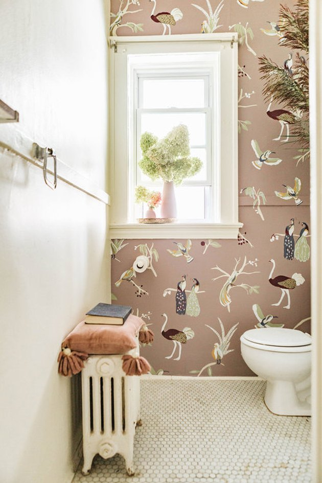 mural on pink wall in small maximalist bathroom with penny tile floor