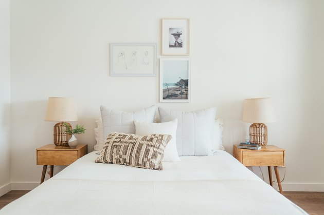 white bedroom with small gallery wall, calming colors, and tan wood nightstands