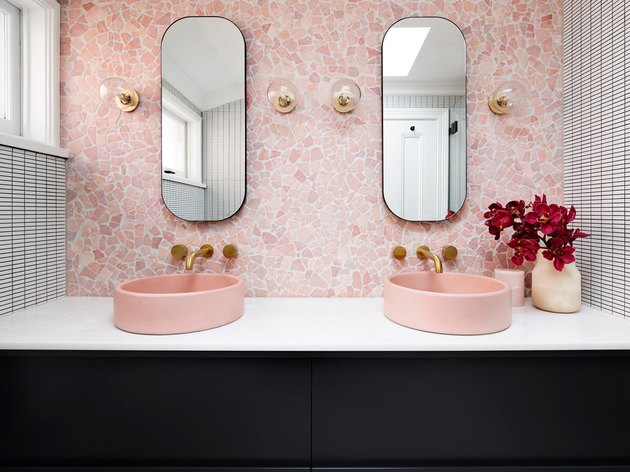 Millennial pink bathroom sink idea with pink backsplash and black vanity cabinet