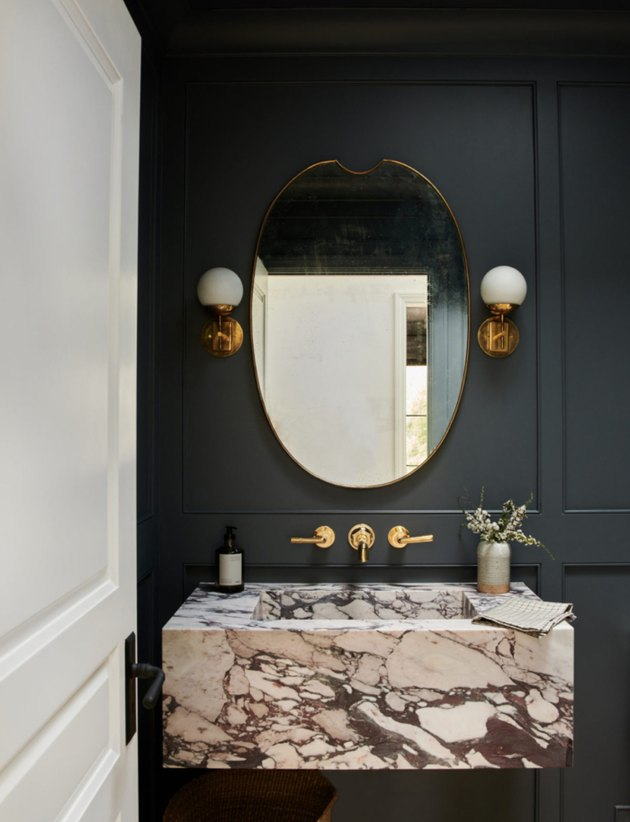 Black maximalist bathroom with marble sink, oval mirror, and gold fixtures
