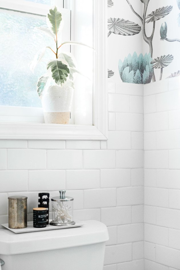 bathroom curtain idea with white subway tile, floral wallpaper, and a window above the toilet