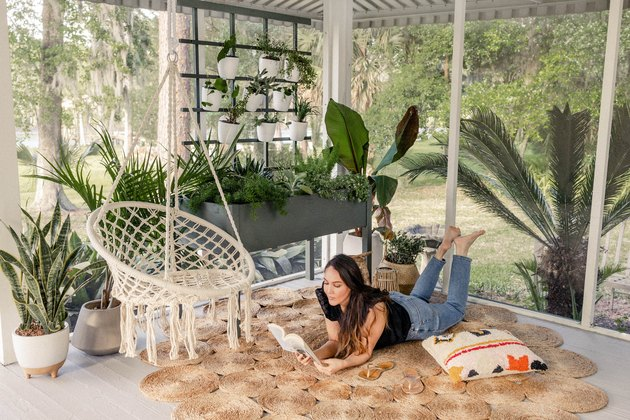 Woman reading book on boho patio with trellis plant wall
