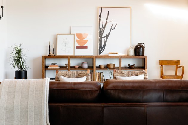 Brown leather sofa in living room paired with natural calming colors and woven wood chairs