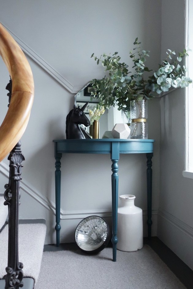 Blue console table with decor along stairs