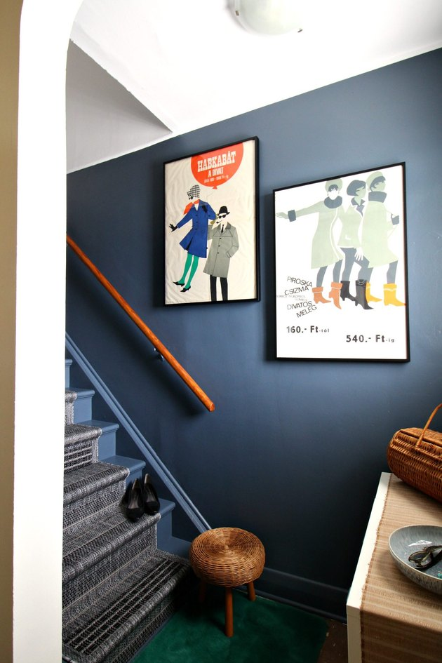 Blue accent wall and vintage posters along stairs