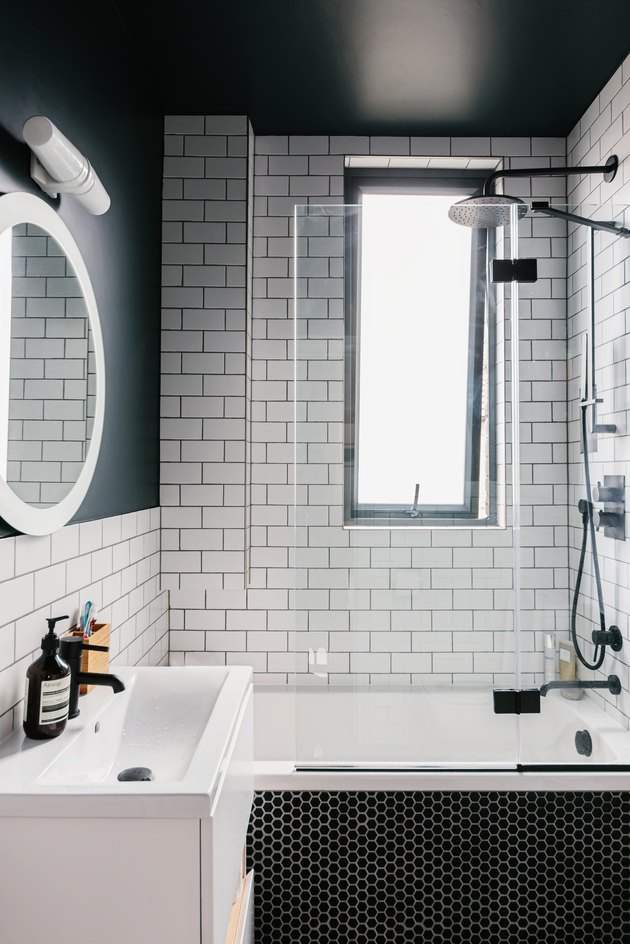 small white sink, round mirror with overhead lighting, black hexagon tile on the bathtub, white subway tile on the wall, deep bathtub with a black faucet and showerhead