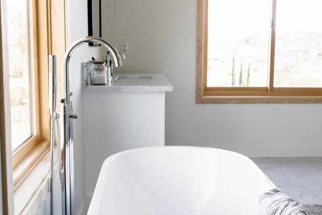 sliding bathroom windows in bathroom with white standing tub and silver faucet