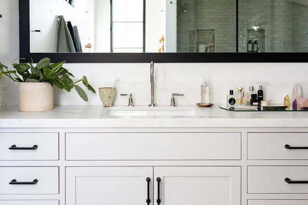 gray bathroom vanity cabinet, undermount sink, silver faucet and handles, rectangular mirror with black trim, vase with green plant, mirrored tray with various bathroom products