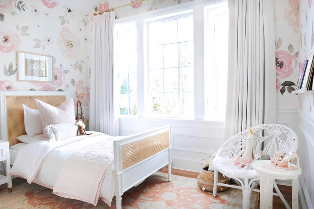 girls bedroom idea with floral patterned wallpaper and cane headboard