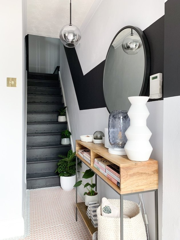Black stairs with color-blocked black painted stripe on wall