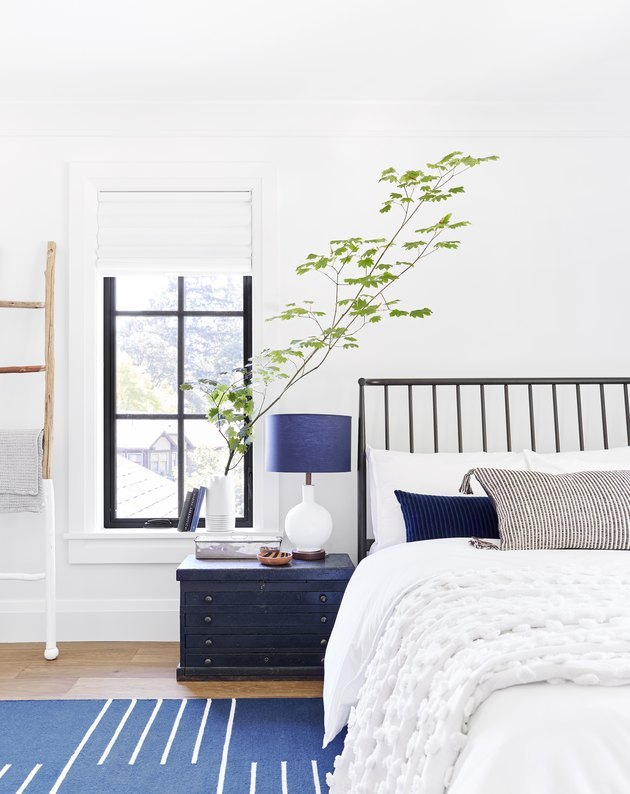 Light, bright rustic blue accents in bedroom with white bedding and large branch