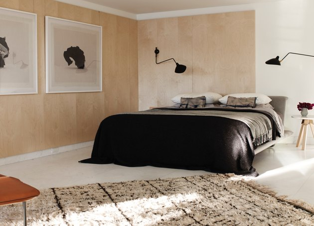 Low platform bed with black and grey linens, black modern sconces black and white large scale photo prints, natural area rug, leather side chair, wooden stool side table, flowers in vase white floors and light wood paneling on walls. Basement Bedroom Ideas
