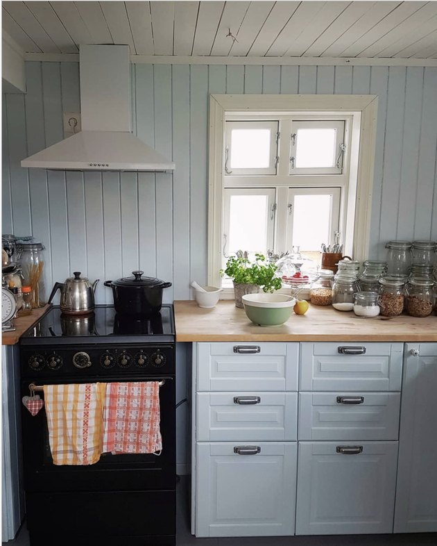 Pale rustic blue kitchen cabinets with shiplap walls