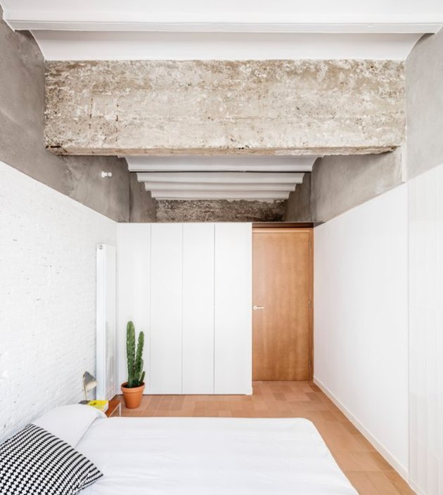 Concrete ceiling, white wood half walls, light wood door and floor, white bed, cactus in terra cotta pot. Basement Bedroom Ideas