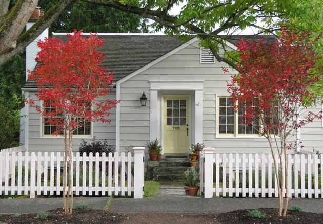 gray traditional home exterior with a white picket fence