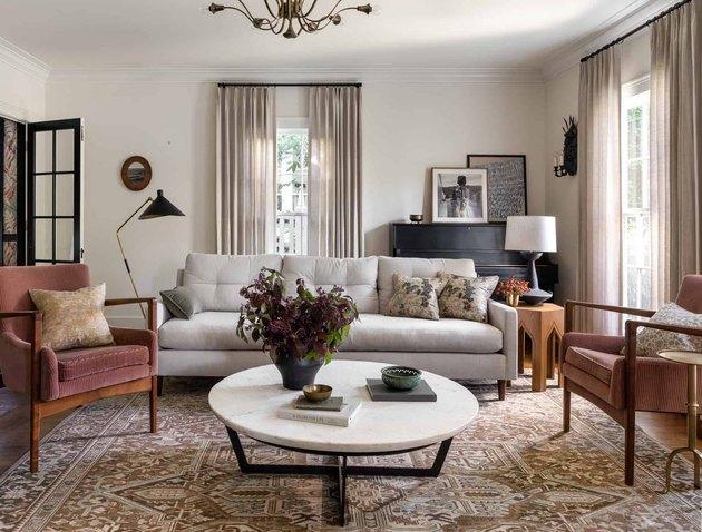 espace salon avec canapé gris, deux chaises et table basse blanche