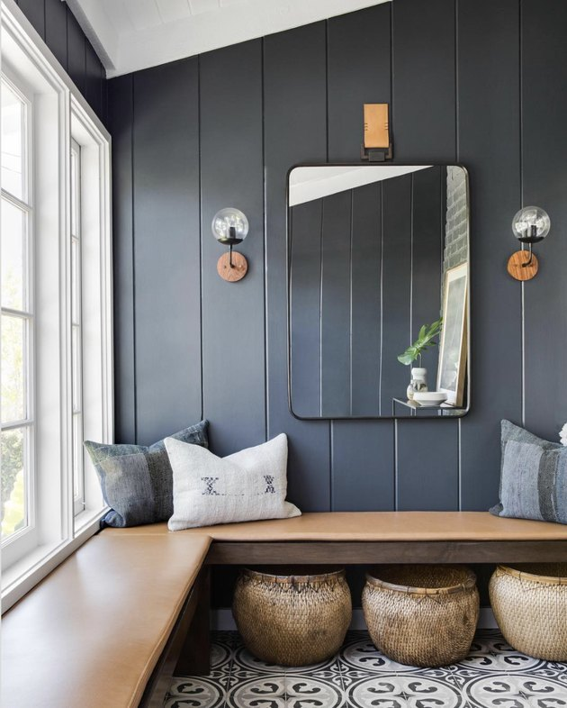 Rustic blue entryway with wood bench and square mirror