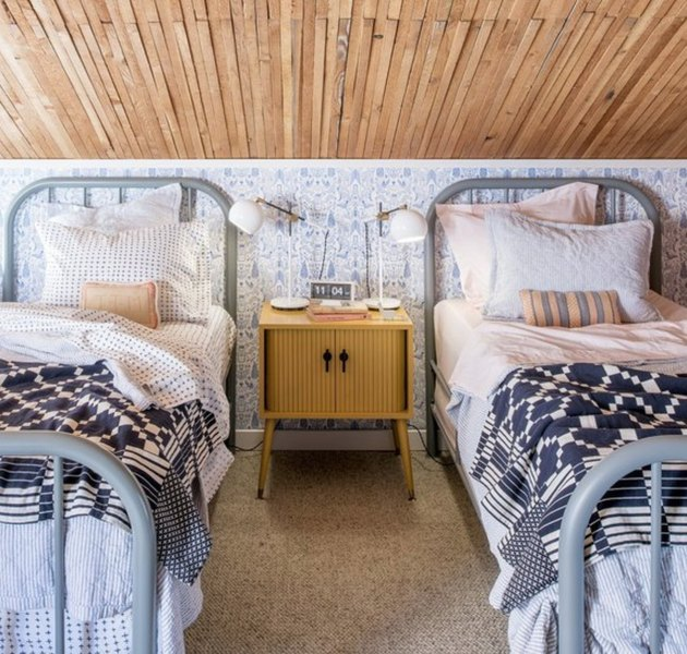 Wood slat ceiling, linoleum floors, twin beds with metal frames and headboards, yellow night stand, white reading lamps, navy and white and patterned linens. Basement Bedroom Ideas